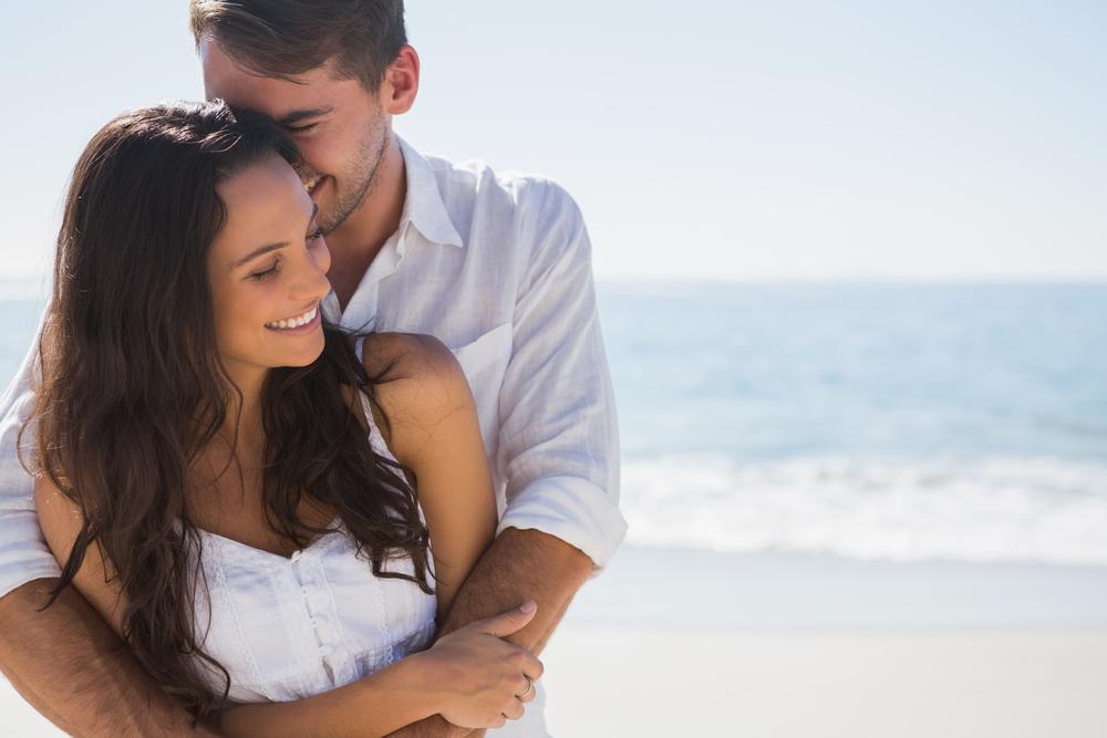 迷人的情侶在沙灘上擁抱